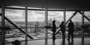 Silhouette of Three Persons Standing inside a building