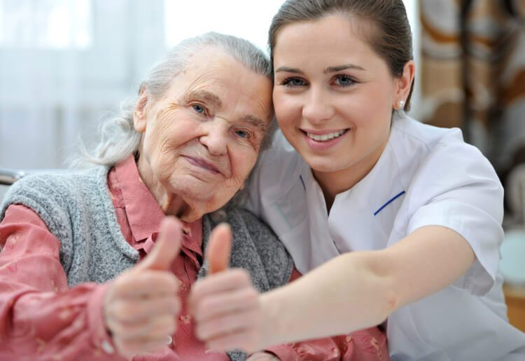 Caregiver and elderly woman giving a thumbs up or okay sign