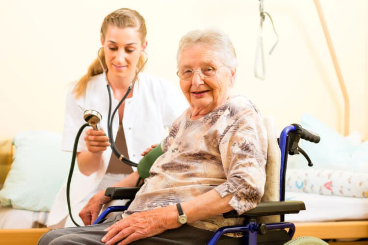 Nanny Taking Blood Pressure of an Elderly Woman on a Wheelchair