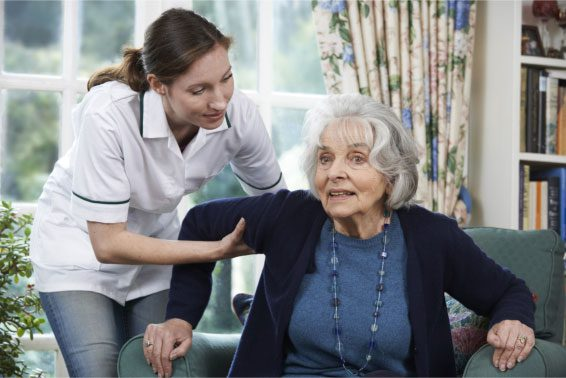 Caregiver Assisisting Old Woman with Alzheimers in Standing