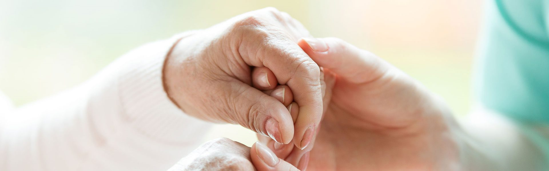 Old-woman-and-caregiver-hold-hands